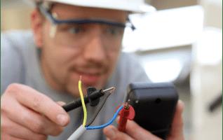 Photo d'illustration des plus du réseau des GRETA dans le secteur du bâtiment et des travaux publics. Jeune homme testant un réseau électrique