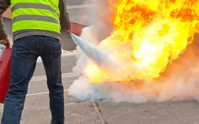 Homme traitant un départ de feu via un extincteur dans le cadre d'une formation.